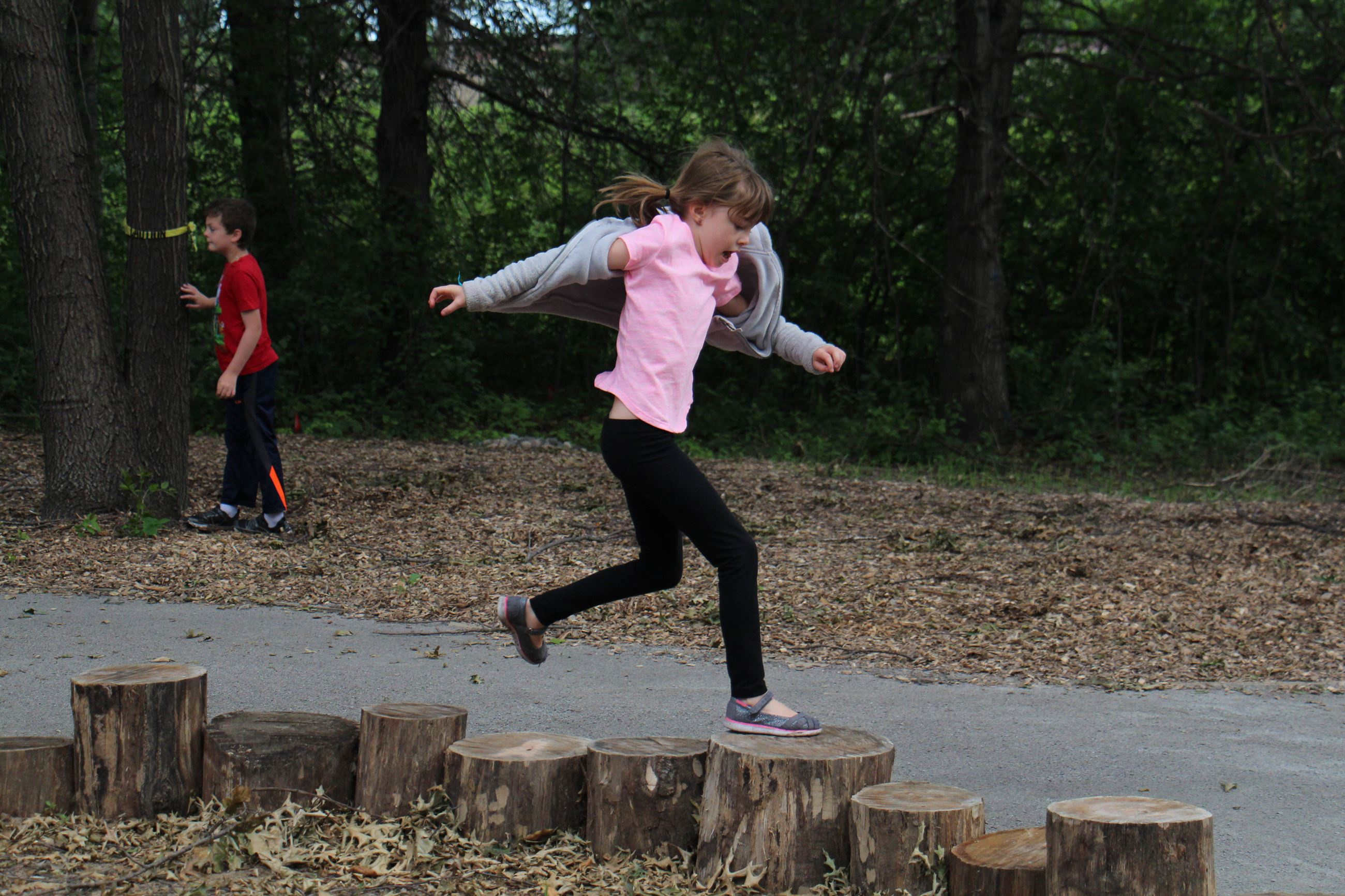 girl jumping on tree stumps