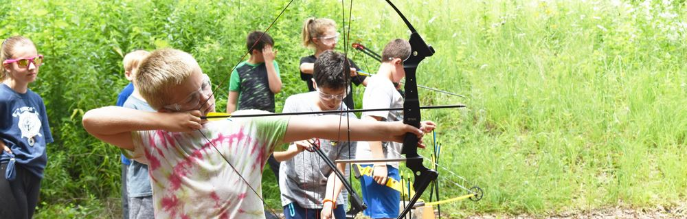 Kids practicing archery at summer camp