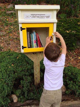Boy opening Little Free Library